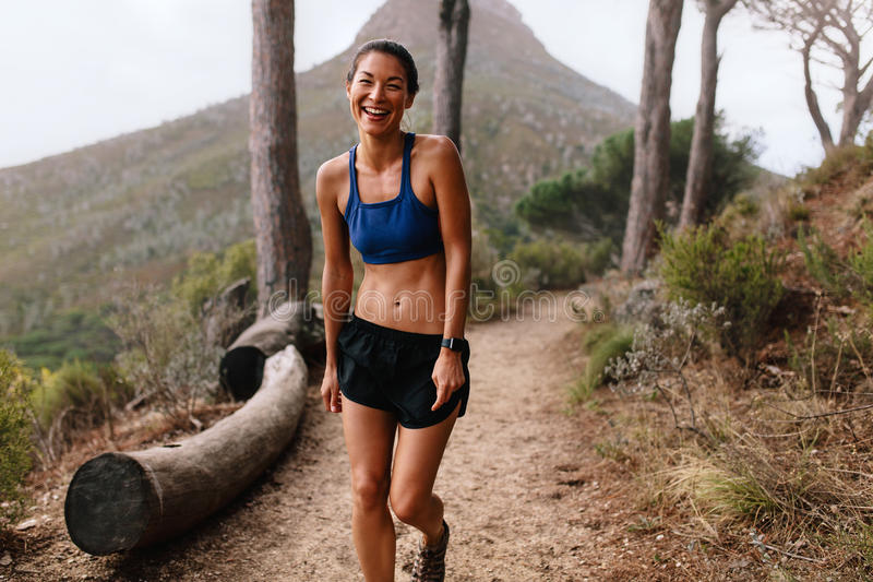 Asian female runner laughing on mountain trail stock photography