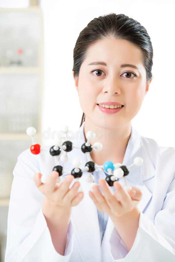 asian female scientist looking at molecular model doing the science research stock image