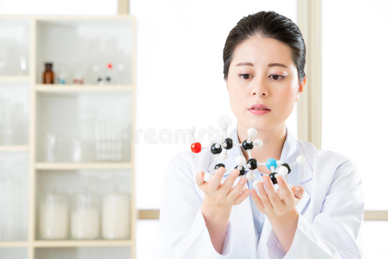 asian female scientist looking at molecular model doing the science research royalty free stock image