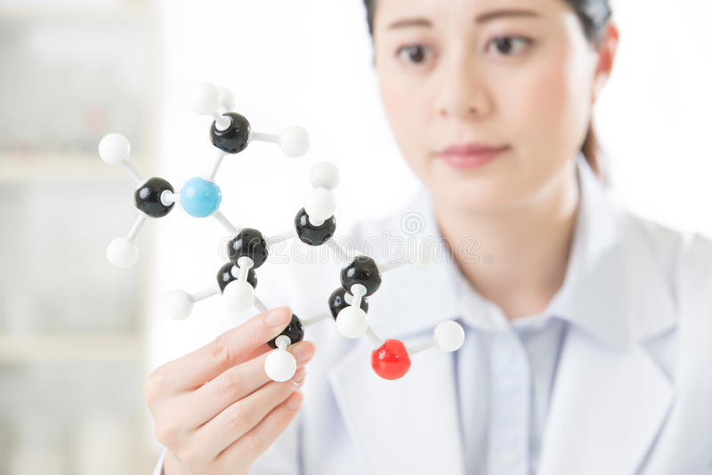 asian female scientist looking at molecular model doing the science research stock photography