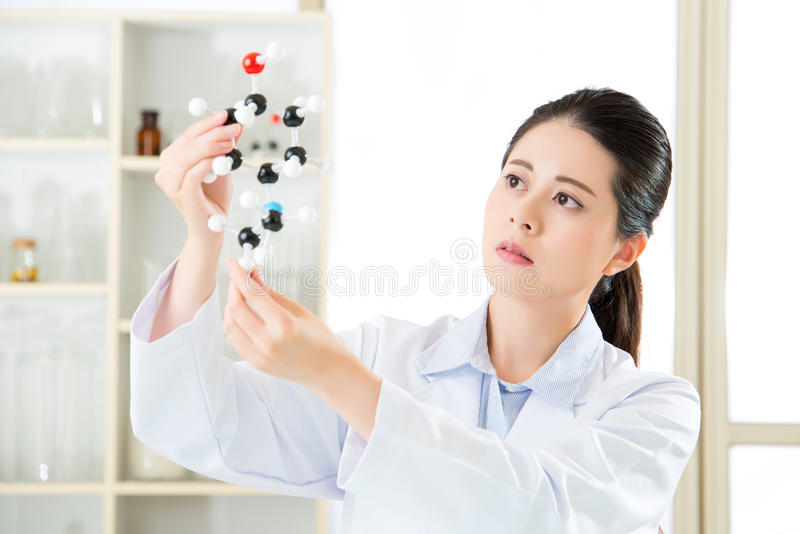 asian female scientist looking at molecular model doing the science research stock photo