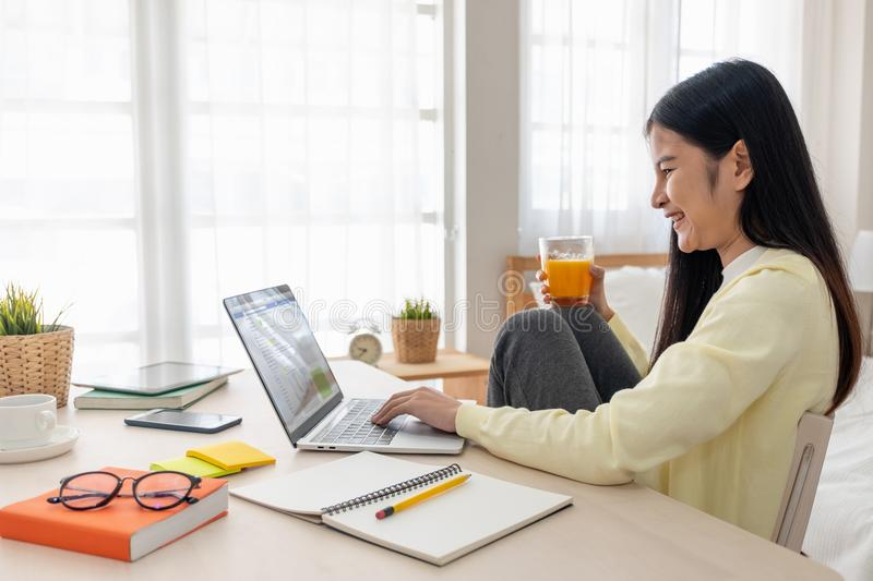 Asian female sit with knees up use social media with laptop on t. Able and drink orange juice in bedroom at home.Work at home concept.work from home.relax stock images