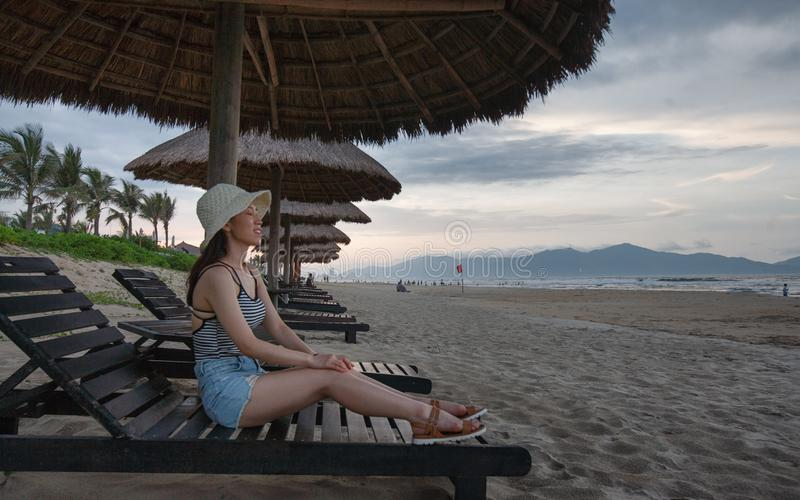 Asian Female Sitting On Beach Recliner with Thatch Umbrella Above royalty free stock photos
