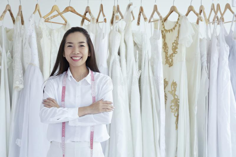 Asian female smilling of bridal store owner standing with her ar stock image