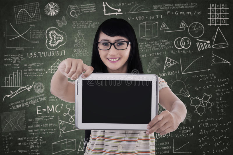 Asian female student show blank e-tablet in class royalty free stock photography