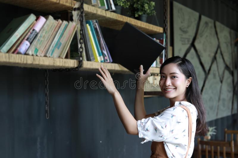 Asian female students holding for section on book shelf royalty free stock images