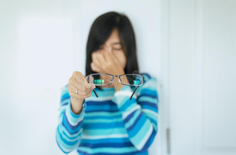 Asian woman suffering from eye pain hand holding eyeglasses and rubs her nose eyes out of fatigue royalty free stock photos