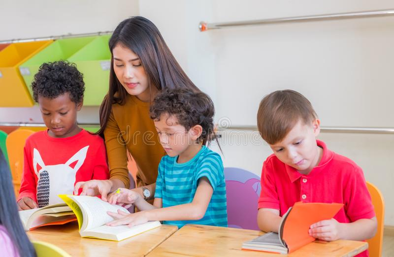 Asian female teacher teaching diversity kids reading book in classroom,Kindergarten pre school concept. stock images