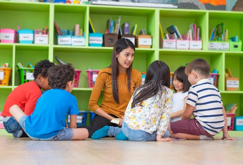 Asian female teacher teaching mixed race diversity group of kids. Reading book sitting on library floor in classroom,Kindergarten pre school concept royalty free stock photo
