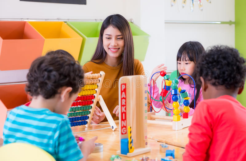 Asian female teacher teaching mixed race kids play toy in classroom,Kindergarten pre school concept stock photos