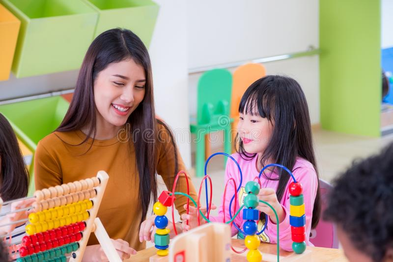 Asian female teacher teaching mixed race kids play toy in classr stock image