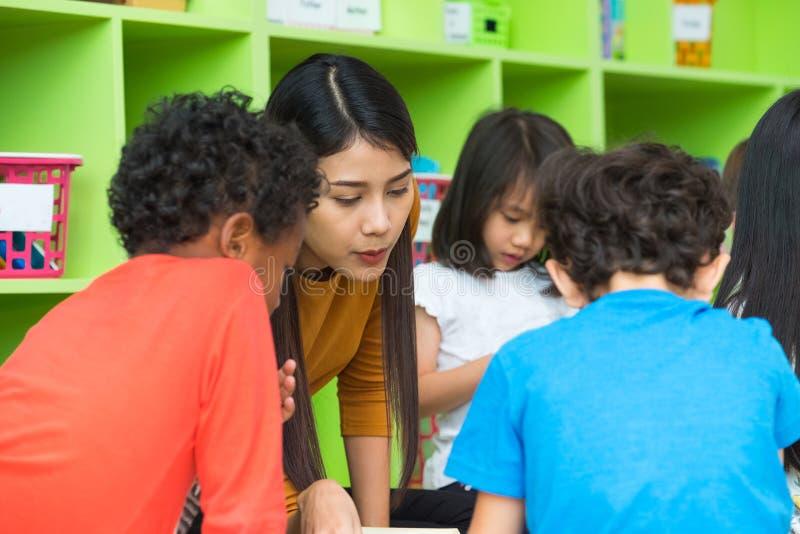 Asian female teacher teaching mixed race kids reading book in cl. Assroom,Kindergarten pre school concept stock image