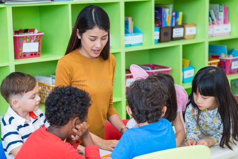 Asian female teacher teaching mixed race kids reading book in cl. Assroom,Kindergarten pre school concept royalty free stock image
