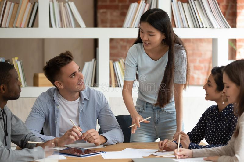 Asian female team leader speak holding meeting with mates royalty free stock photos