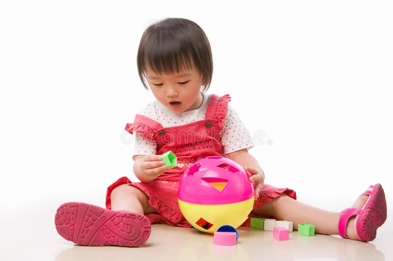 Asian female toddler playing. On the floor alone stock images