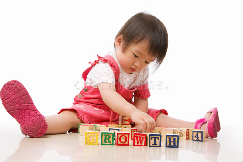 Asian female toddler playing. On the floor alone. PS: main focus on the word 'growth royalty free stock image