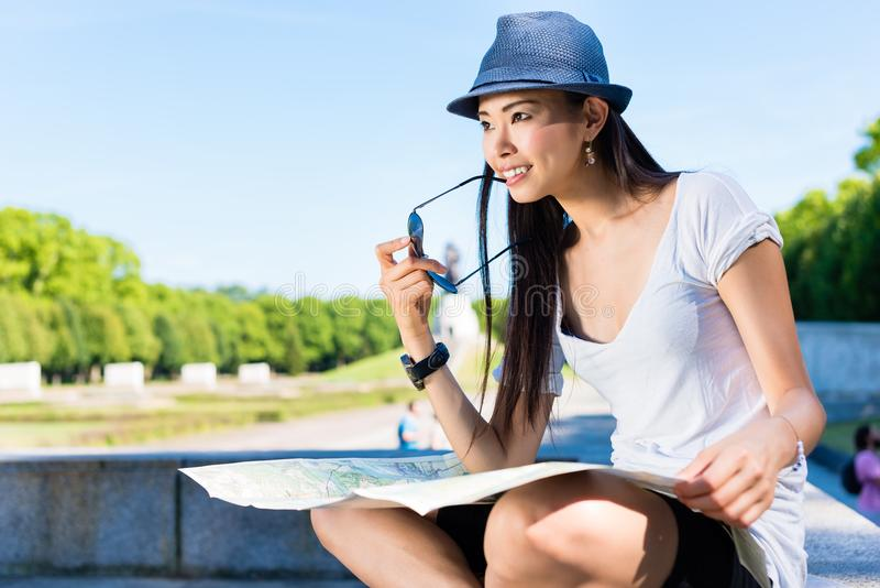 Asian female tourist holding a map outdoors. Asian young female tourist looking at camera while holding a map outdoors in the park stock photography