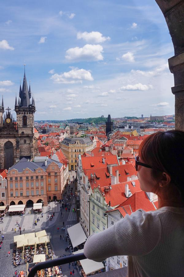 Asian female tourist looking down old town square from observatory of astronomical clock tower in Prague. Czech stock photos