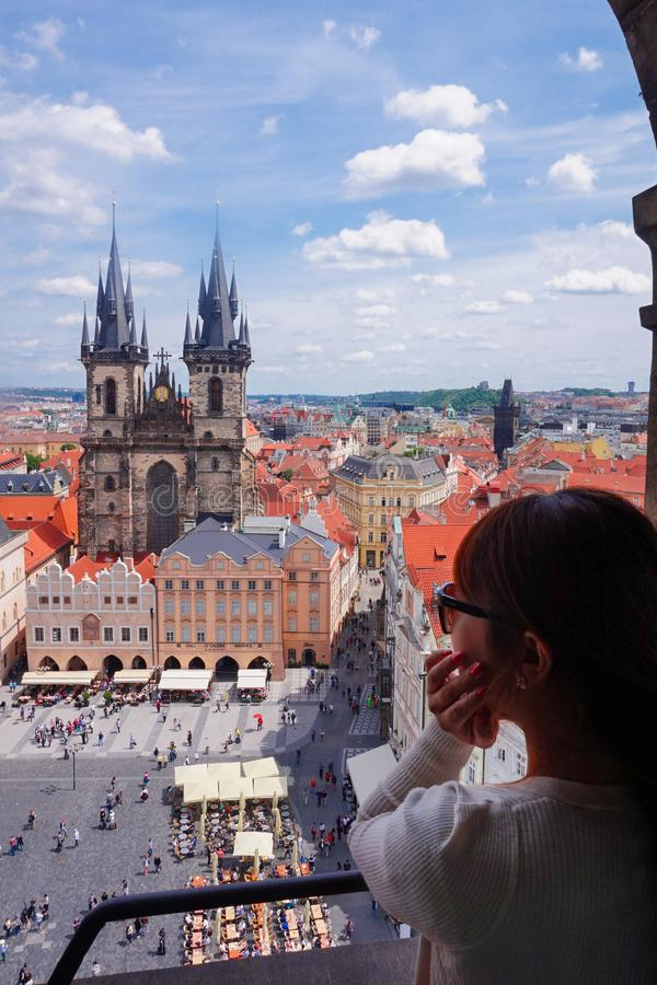 Asian female tourist looking down old town square from observatory of astronomical clock tower in Prague. Czech stock photo