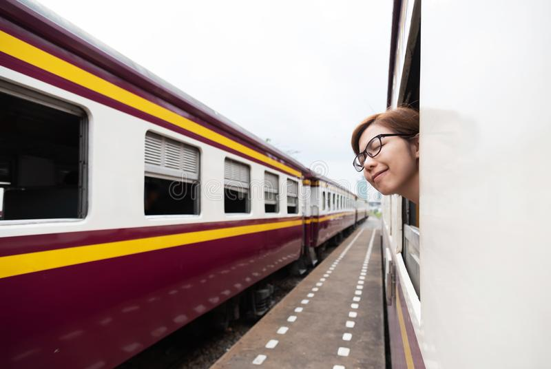 Asian female traveler breathing fresh air. Relaxed Asian female traveler wear glasses breathing fresh air at outside of the train. Smiling face. Travel Concept royalty free stock image