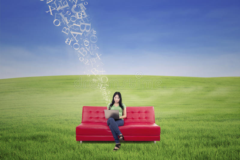Asian female using laptop on sofa with flying letters outdoor