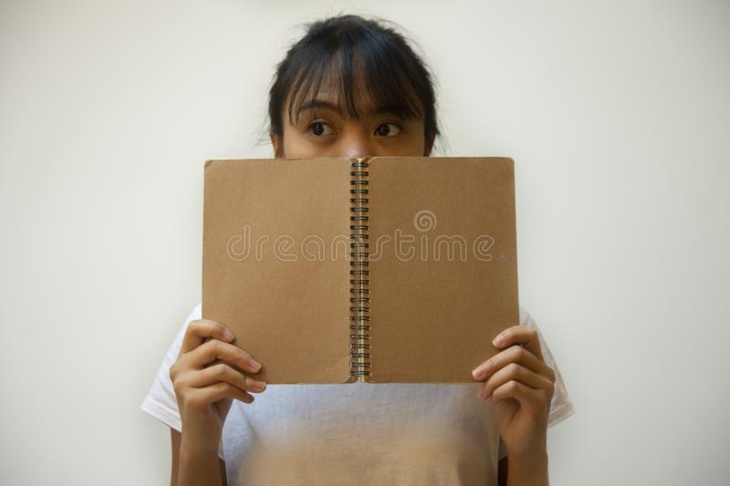 Asian Filipino cute teenager girl hiding her face behind brown notebook background royalty free stock image