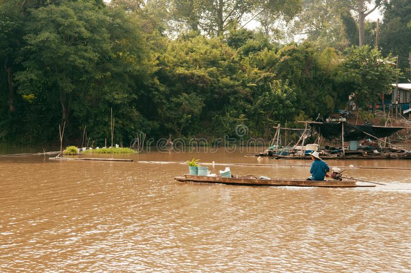 Asian fisherman on wooden longtail boat in nature river royalty free stock photography