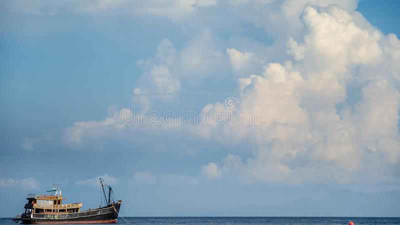 Fishing boat in the sea with big cloud stock photos