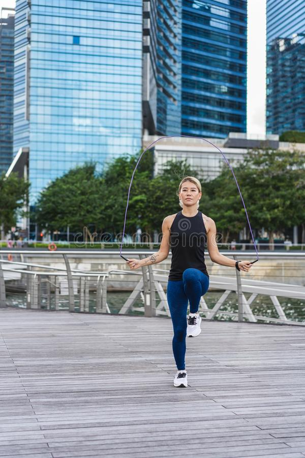 Girl doing exercise with jump rope stock images