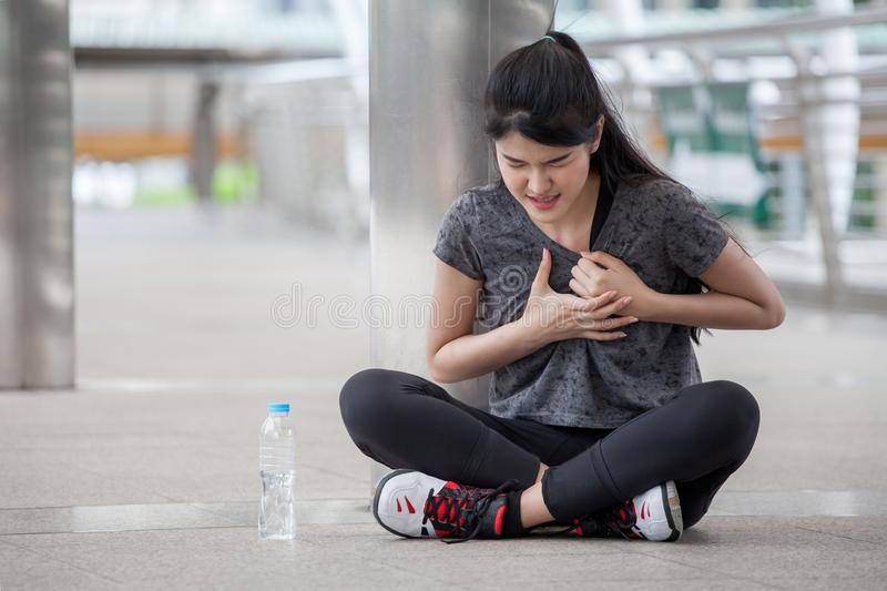 asian fitness young woman have chest pains or heart attack in workout exercising on street in urban city . Tired sport girl rest royalty free stock photo