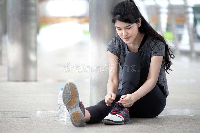 asian fitness young woman runner tying shoelaces before running workout exercising with a water bottle on street in urban city . stock photo