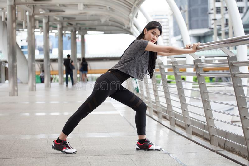 Asian fitness young woman stretching leg on a rail bridge workout exercising on street in urban city . runner sport girl warm up. Female athlete cool down royalty free stock photos