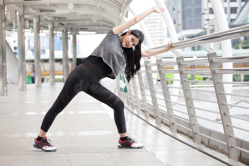 Asian fitness young woman stretching leg on a rail bridge workout exercising on street in urban city . runner sport girl warm up. Female athlete cool down stock image