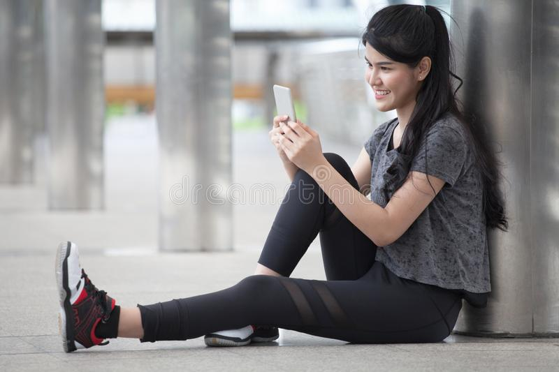 Asian fitness young woman taking a break after workout exercising using smartphone on street in urban city . sport girl rest after. Exhausted. female athlete stock photography