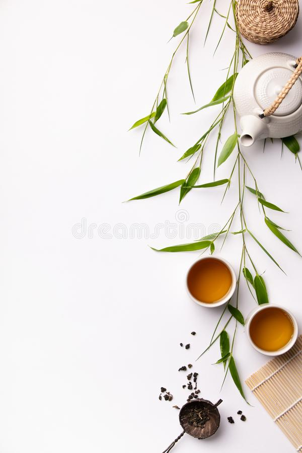Asian food background set with green tea, cups and teapot with bamboo branches royalty free stock photos