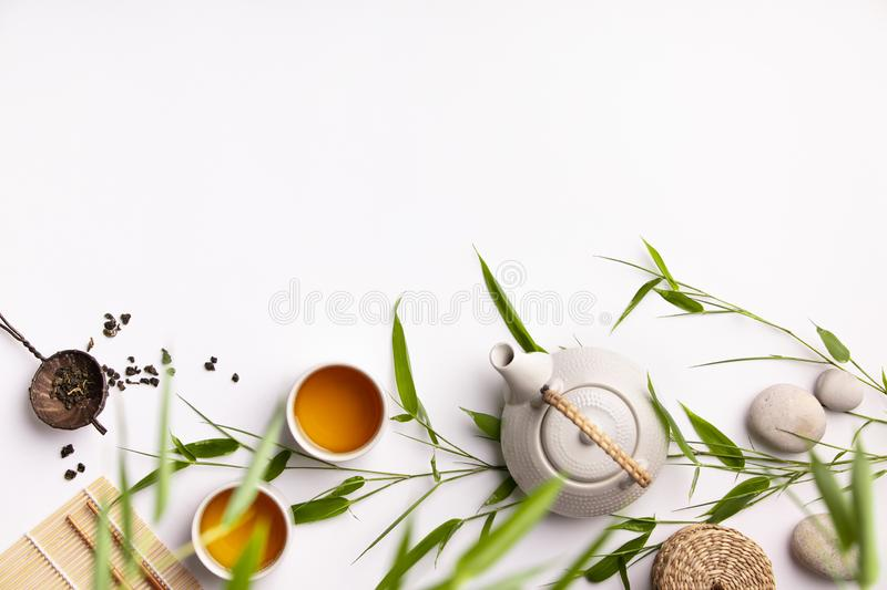Asian food background set with green tea, cups and teapot with bamboo branches royalty free stock image