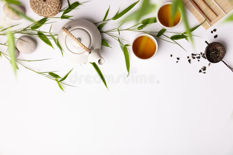 Asian food background set with green tea, cups and teapot with bamboo branches stock photos