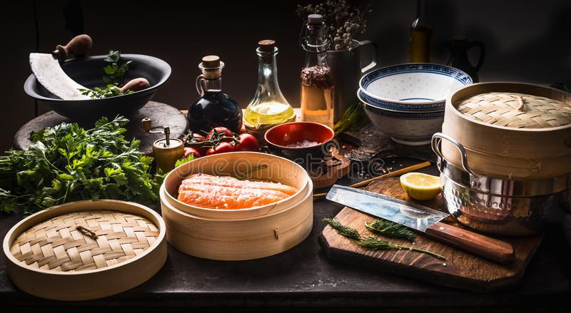 Asian food . Bamboo steamer with salmon fillet on dark rustic kitchen with various, seasoning, tools and ingredients . Cooking royalty free stock images