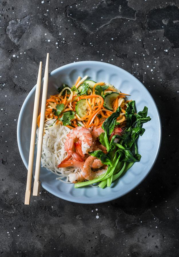 Asian food bowl - rice noodles, shrimp, cabbage bok choy and quickly pickled vegetables carrots, cucumbers, daikon salad on a dark. Background, top stock images