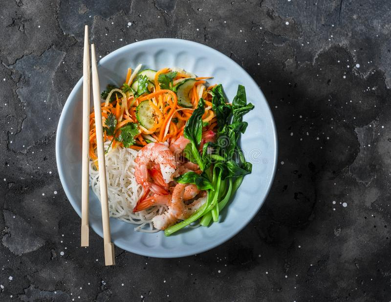Asian food bowl - rice noodles, shrimp, cabbage bok choy and quickly pickled vegetables carrots, cucumbers, daikon salad on a dark. Background, top royalty free stock photography