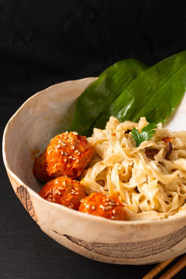 Asian Food concept homemade oriental egg noodles and spicy meatballs in ceramic bowl on black background stock images
