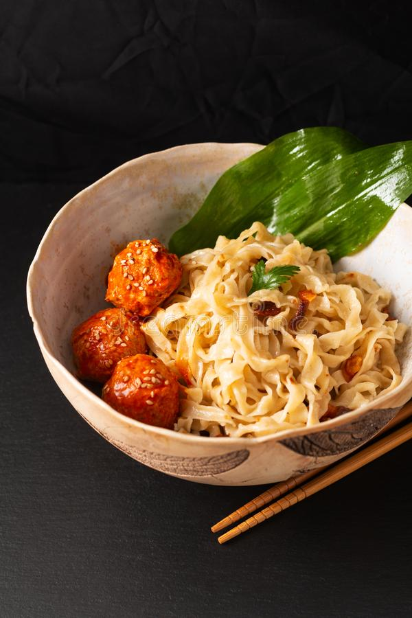 Asian Food concept homemade oriental egg noodles and spicy meatballs in ceramic bowl on black background stock image