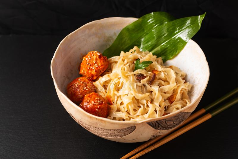 Asian Food concept homemade oriental egg noodles and spicy meatballs in ceramic bowl on black background royalty free stock image
