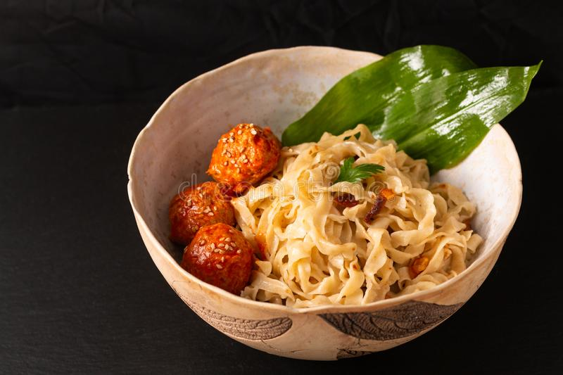 Asian Food concept homemade oriental egg noodles and spicy meatballs in ceramic bowl on black background stock photography