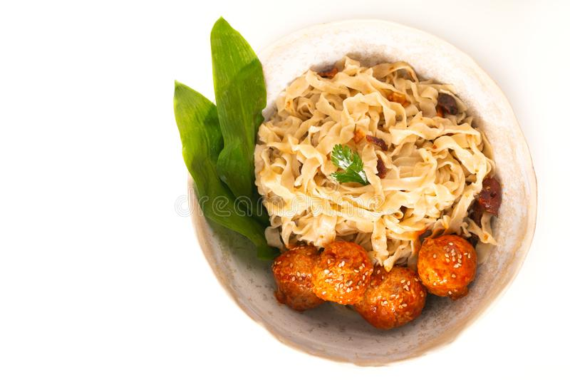 Asian Food concept homemade oriental egg noodles and spicy meatballs in ceramic bowl on white background stock photos