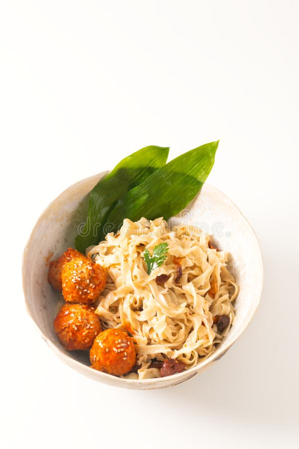 Asian Food concept homemade oriental egg noodles and spicy meatballs in ceramic bowl on white background stock photography