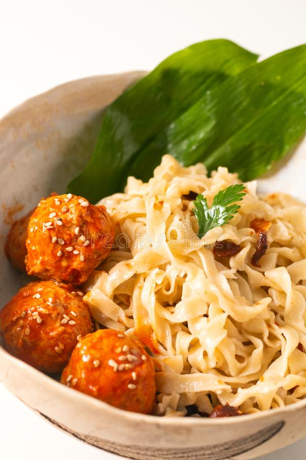 Asian Food concept homemade oriental egg noodles and spicy meatballs in ceramic bowl on white background stock image