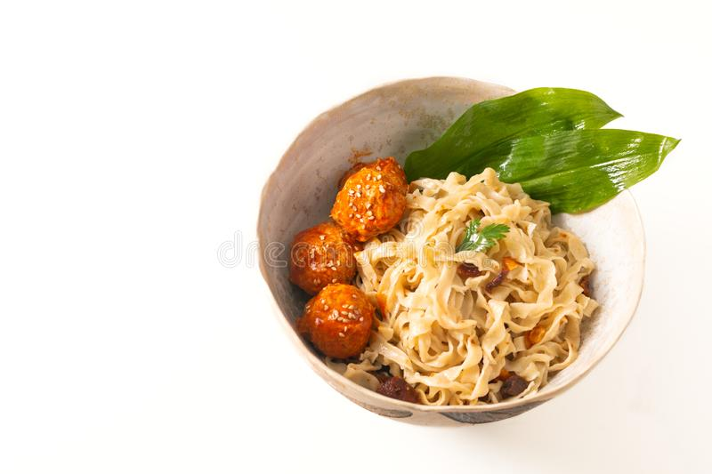 Asian Food concept homemade oriental egg noodles and spicy meatballs in ceramic bowl on white background royalty free stock photography