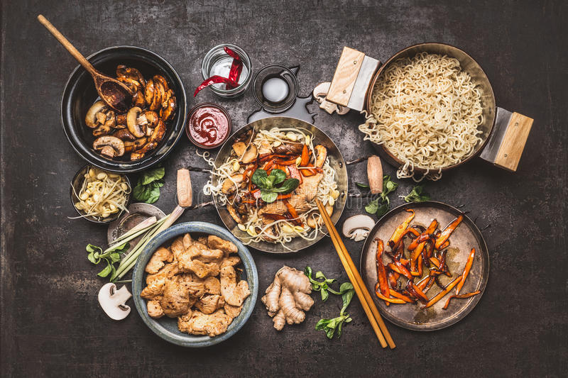 Asian food cooking. Wok with noodles chicken stir fry and vegetables ingredients with spices ,sauces and chopsticks on dark rustic royalty free stock photography
