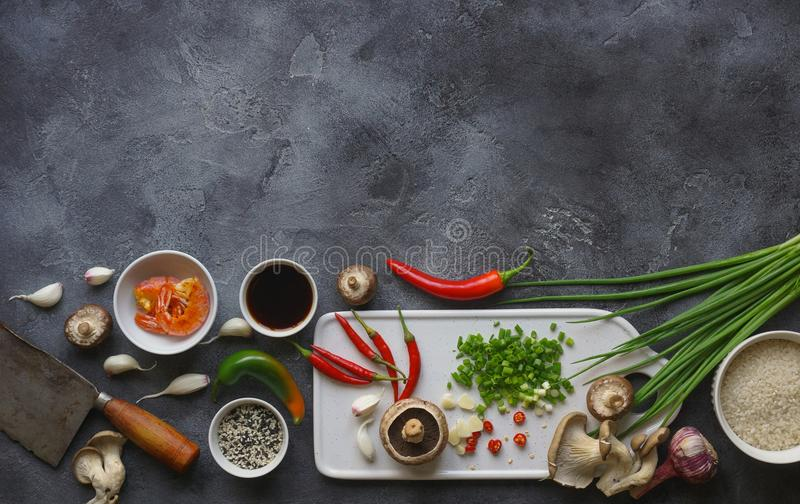 Asian food on a dark background, Wok rice with shrimps and mushrooms, During preparation royalty free stock photography